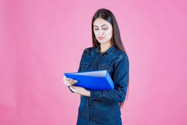 Jonge vrouw die een bedrijfsrapport houdt en denkt