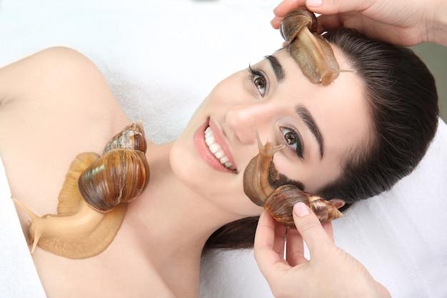 Jonge vrouw die een behandeling met gigantische achatina-slakken in de schoonheidssalon ondergaat