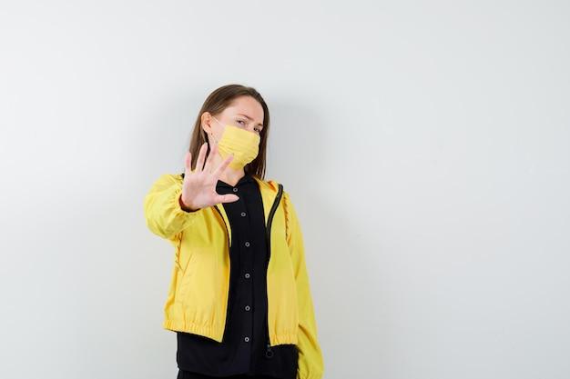 Jonge vrouw die een beperkingsgebaar toont