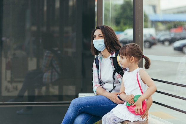 Jonge vrouw die een beschermend masker draagt met haar dochter die wacht op een openbare bus bij het busstation