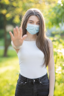Jonge vrouw die een beschermend masker in het park draagt