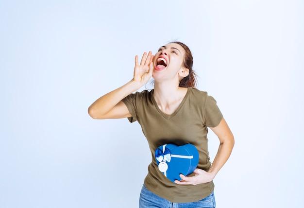 Jonge vrouw die een blauwe geschenkdoos in de vorm van een hart vasthoudt en hardop schreeuwt