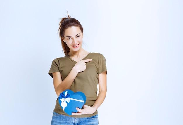 Jonge vrouw die een blauwe geschenkdoos met een gehoorde vorm vasthoudt en naar iemand wijst