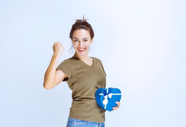 Jonge vrouw die een blauwe geschenkdoos met een gehoorde vorm vasthoudt en zich tevreden voelt