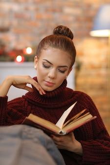 Jonge vrouw die een boek in de bank leest