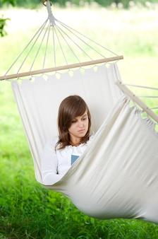 Jonge vrouw die een boek in hangmat leest