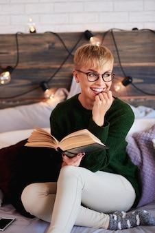 Jonge vrouw die een boek in slaapkamer leest