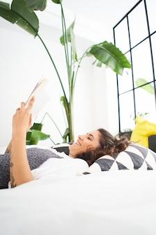 Jonge vrouw die een boek leest in de gezellige kamer leren studeren onderwijs leesboek