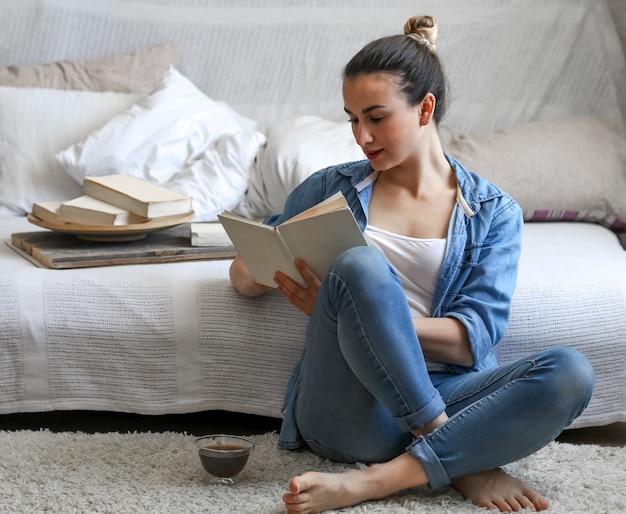 Jonge vrouw die een boek leest in een gezellige kamer