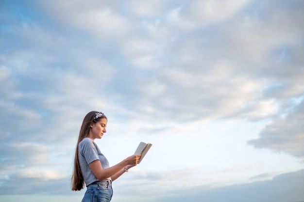 Jonge vrouw die een boek met blauwe hemel leest