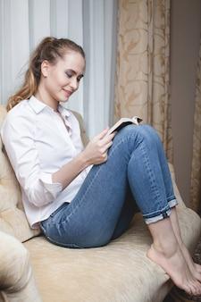 Jonge vrouw die een boek op bank leest