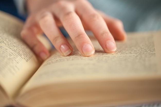 Jonge vrouw die een boek opent en leest