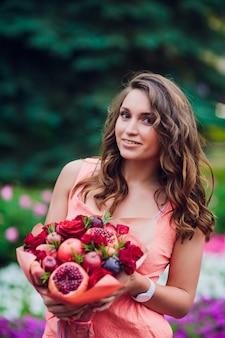 Jonge vrouw die een boeket van fruit en bessen houdt