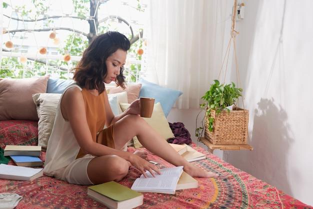 Jonge vrouw die een boekzitting op haar bed met een kop van een drank leest