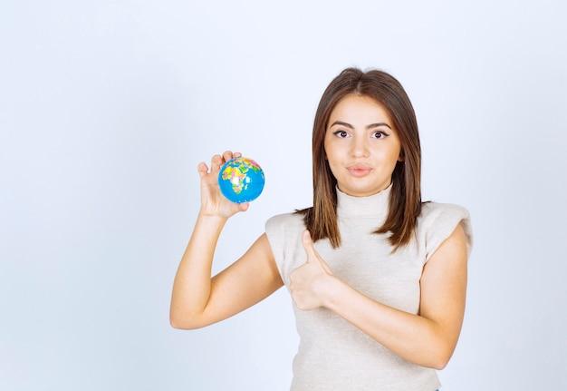 Jonge vrouw die een bol van de aardebol houdt en een duim toont.