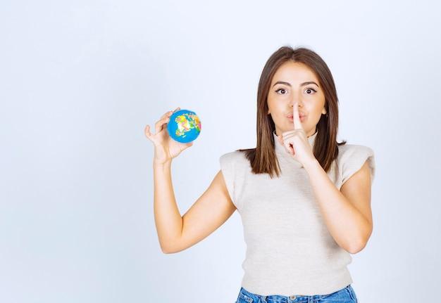 Jonge vrouw die een bol van de aardebol houdt en stil teken doet.