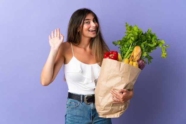 Jonge vrouw die een boodschappentas houdt die met hand met gelukkige uitdrukking groeten