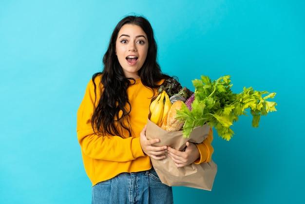 Jonge vrouw die een boodschappentas houdt die op blauw met verrassingsgelaatsuitdrukking wordt geïsoleerd