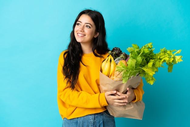 Jonge vrouw die een boodschappentas houdt die op blauwe muur wordt geïsoleerd die een idee denkt terwijl het opzoeken