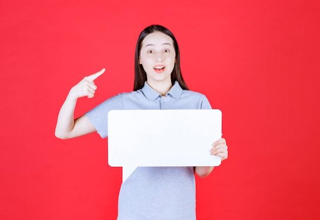 Jonge vrouw die een bord vasthoudt en met de vinger naar zichzelf wijst