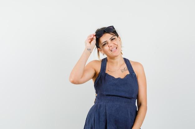 Jonge vrouw die een bril op het hoofd houdt in een donkerblauwe jurk en er prachtig uitziet