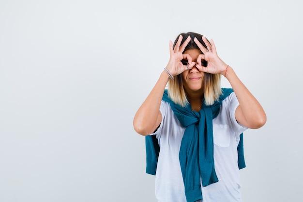 Jonge vrouw die een brilgebaar in wit t-shirt toont en er serieus uitziet, vooraanzicht.