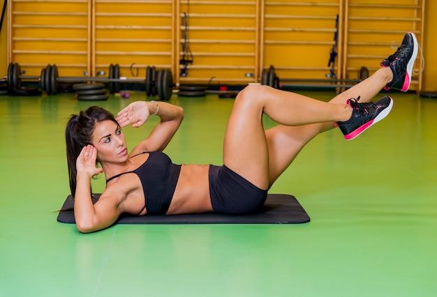 Jonge vrouw die een buikoefening doet