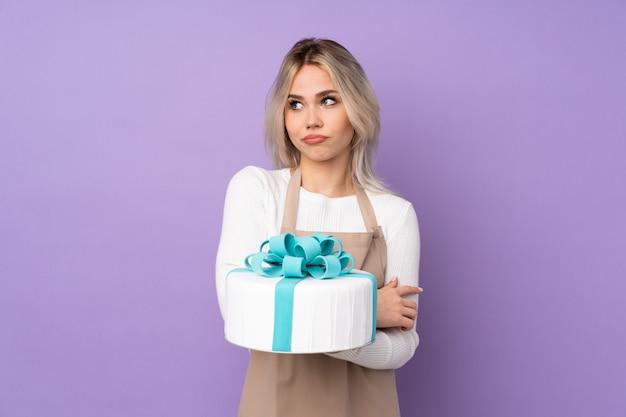 Jonge vrouw die een cake over geïsoleerde muur houdt
