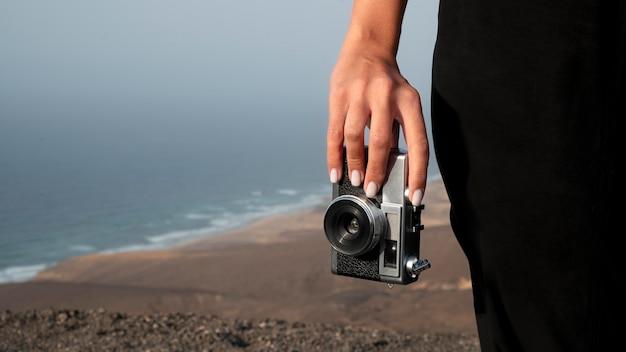 Jonge vrouw die een camera gebruikt tijdens haar vakantie
