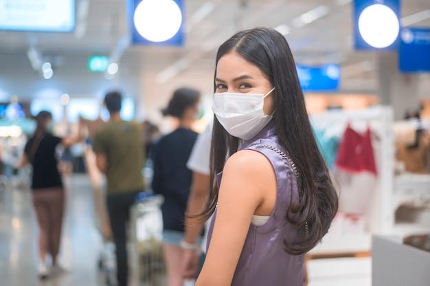Jonge vrouw die een chirurgisch masker draagt dat in de rij dichtbij kassateller in supermarkt, covid-19 en pandemisch concept wacht