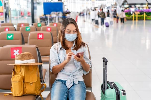 Jonge vrouw die een chirurgisch masker draagt en een mobiele telefoon gebruikt tijdens het wachten op een vlucht op de luchthaven