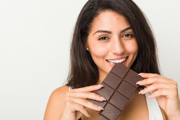 Jonge vrouw die een chocoladetablet houdt