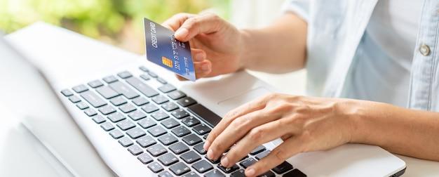 Jonge vrouw die een creditcard houdt en laptop met behulp van