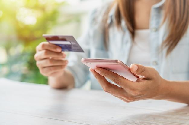 Jonge vrouw die een creditcard houdt en smartphone gebruikt voor het maken van online betalingen winkelen