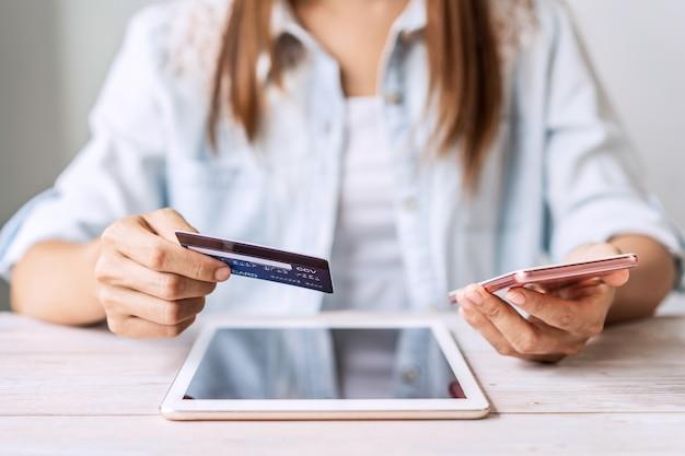 Jonge vrouw die een creditcard houdt en telefoon gebruikt