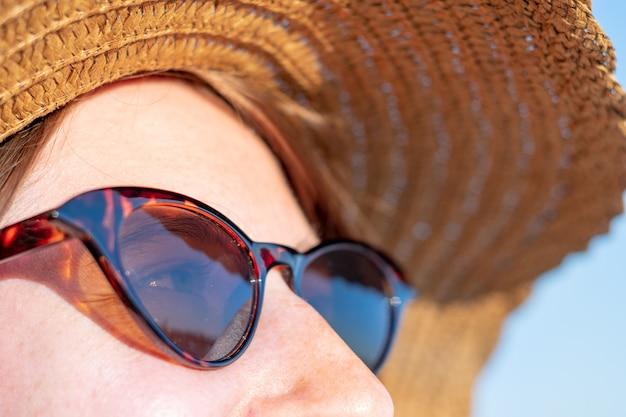 Jonge vrouw die een de zomerhoed en zonnebril draagt