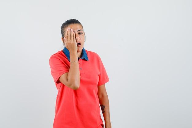 Jonge vrouw die een deel van het gezicht bedekt met dient rode t-shirt in en kijkt moe, vooraanzicht.
