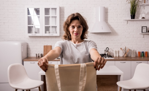 Jonge vrouw die een doekzak houdt. bij de keuken. ik ben geen plastic. campagne om het gebruik van plastic zakken te verminderen. zero waste