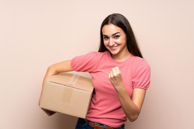 Jonge vrouw die een doos houdt om het naar een andere plaats te verplaatsen