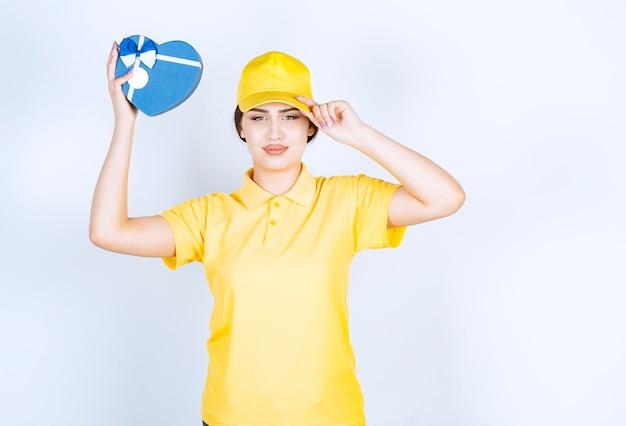 Jonge vrouw die een doos in de vorm van een hart vasthoudt terwijl ze haar hoed recht maakt