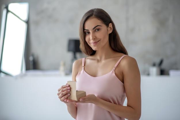 Jonge vrouw die een doos met schoonheidsmiddelen opent