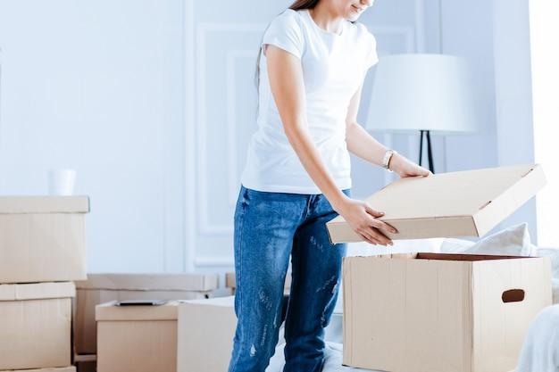 Jonge vrouw die een doos opent in een nieuw appartement dat verhuist naar een nieuw appartement