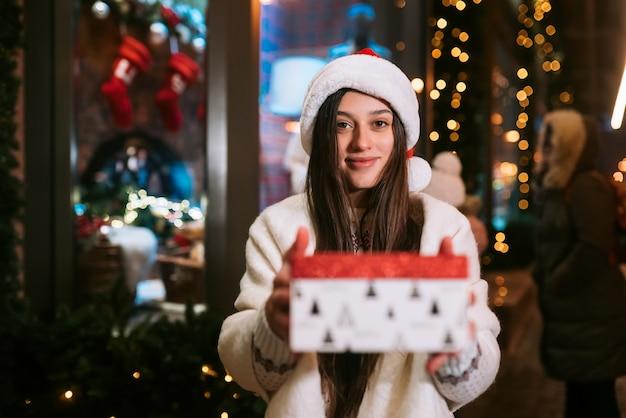 Jonge vrouw die een doos voor je geeft buiten in de winterstraat geschenkuitwisselingsconcept.