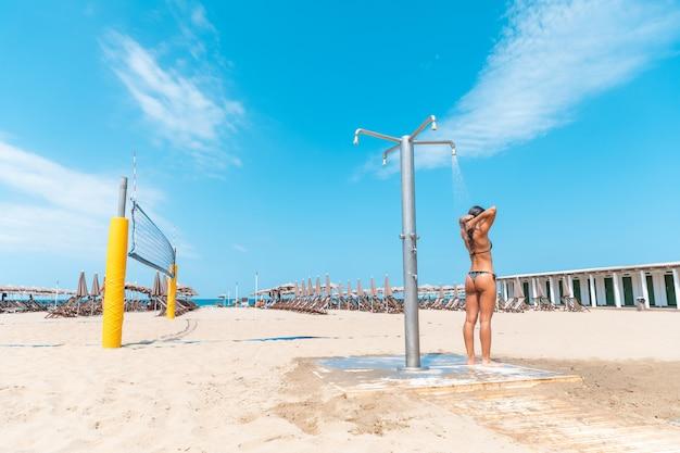 Jonge vrouw die een douche in het strand heeft na het zwemmen en zonnebaden