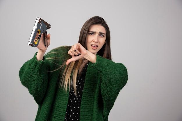 Jonge vrouw die een duim naar beneden toont en een werkend hulpmiddel houdt.