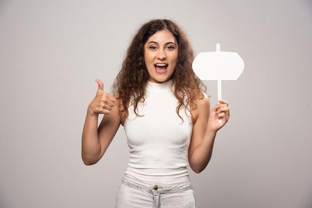 Jonge vrouw die een duim toont en lege witte affiche houdt. hoge kwaliteit foto