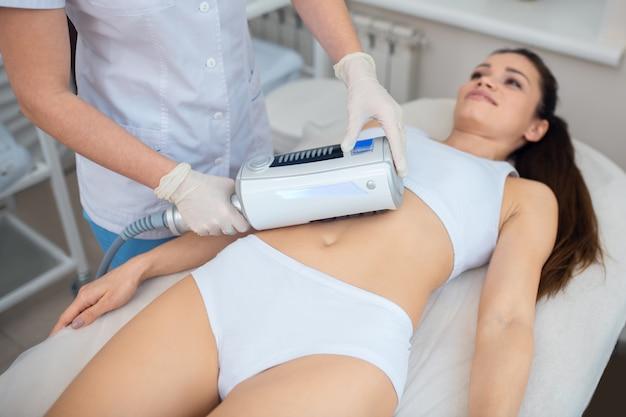 Jonge vrouw die een echografie-massagetherapie krijgt