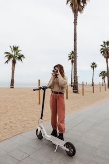 Jonge vrouw die een elektrische autoped berijdt