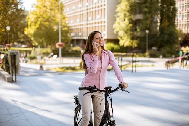 Jonge vrouw die een elektrische fiets berijdt en mobiele telefoon met behulp van