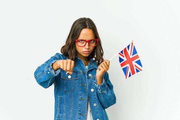 Jonge vrouw die een engelse vlag houdt die op witte muur wordt geïsoleerd die een klap, woede, vechten wegens een argument, boksen gooit